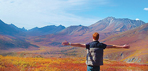 Person stretching his arms out in front of mountains