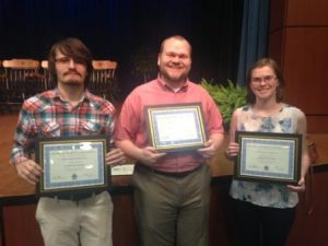 Three students holding their awards
