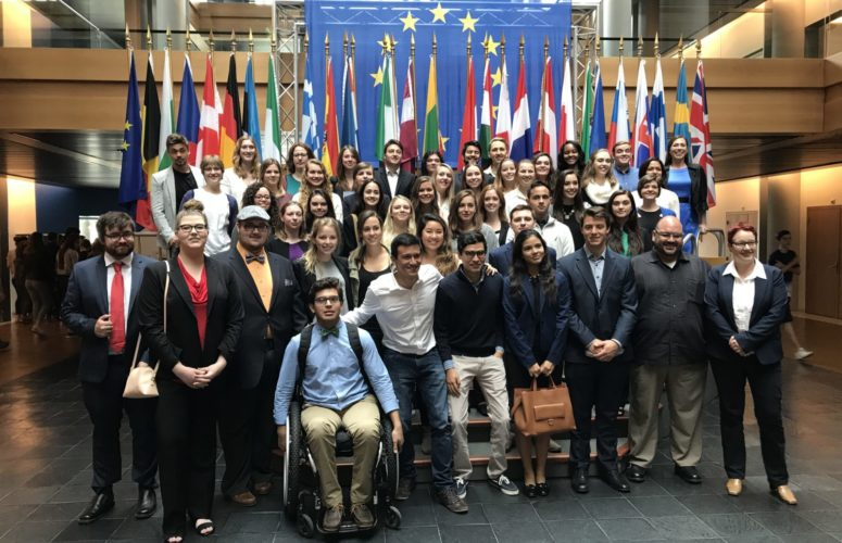 Group photo of students standing in front of flags