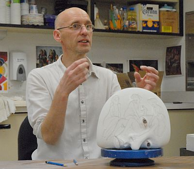 Professor speaking about the sculpture's face to the students