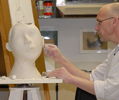 Professor putting details on the sculpture's ear