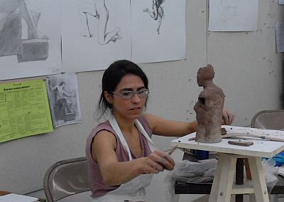 Professor working on her sculpture, which is a human's body