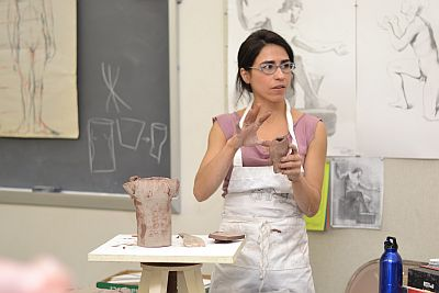 Professor holding her sculpture and speaking about it
