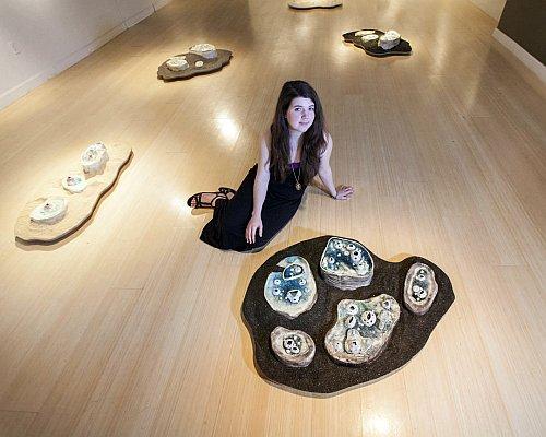 Haley Douglas (photo by H. Gordon Humphries), posing with artwork