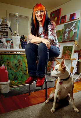 Patty Brady sitting with a dog while surrounded by art
