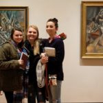 Three students posed in front of art work