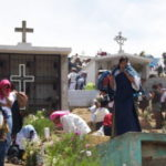 People crowded around tombs with crosses