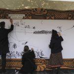 Three people drawing on a board