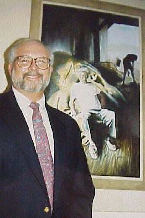 L. Stephen Guyton standing beside painting