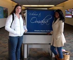 """Two people standing in front of """"Welcome to Omaha"""" sign"""