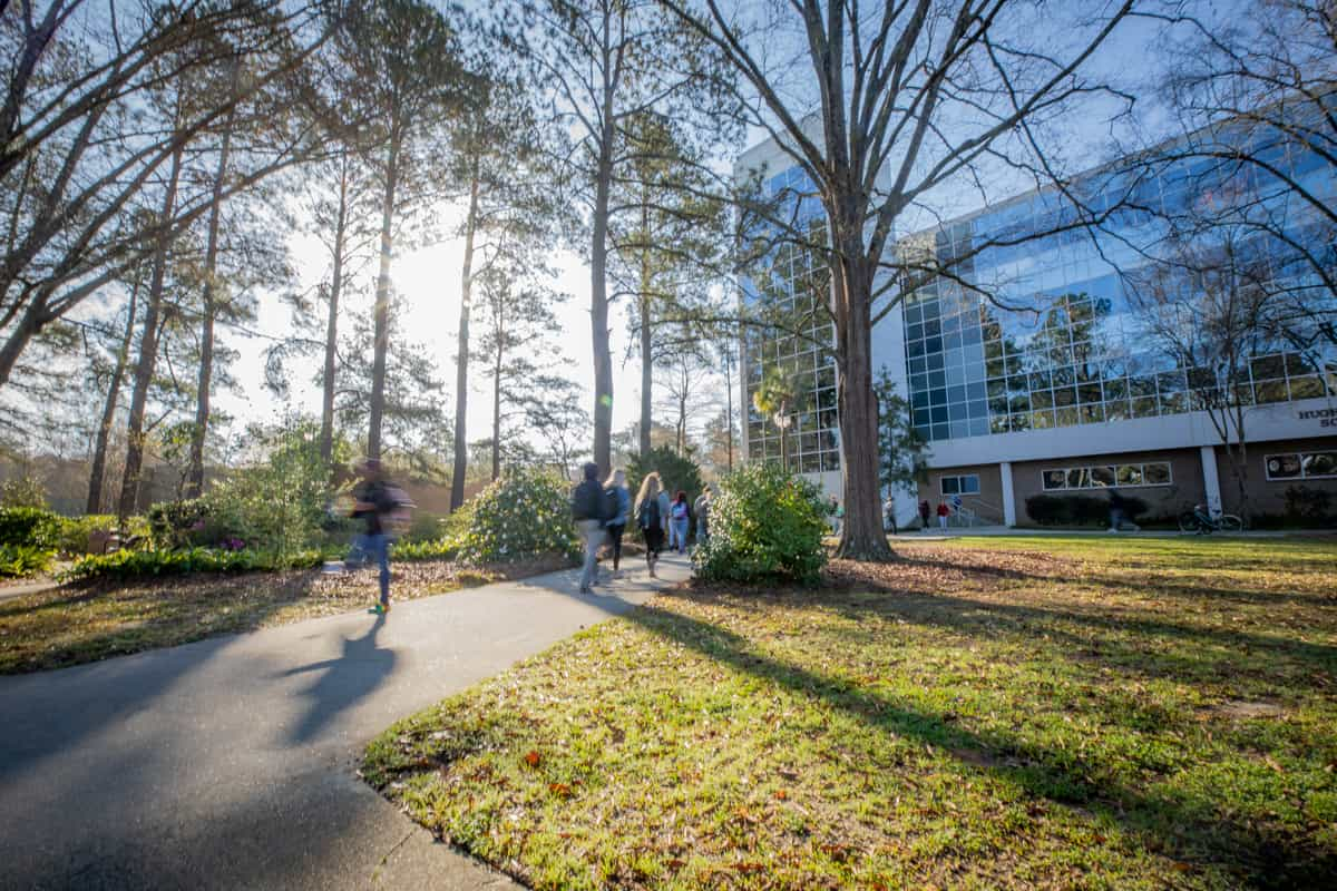 Students walk across FMU's campus on a sunny day.