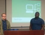 Two men standing with Tut it Up Powerpoint