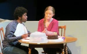 Two people sitting at a table during Love Sick scene