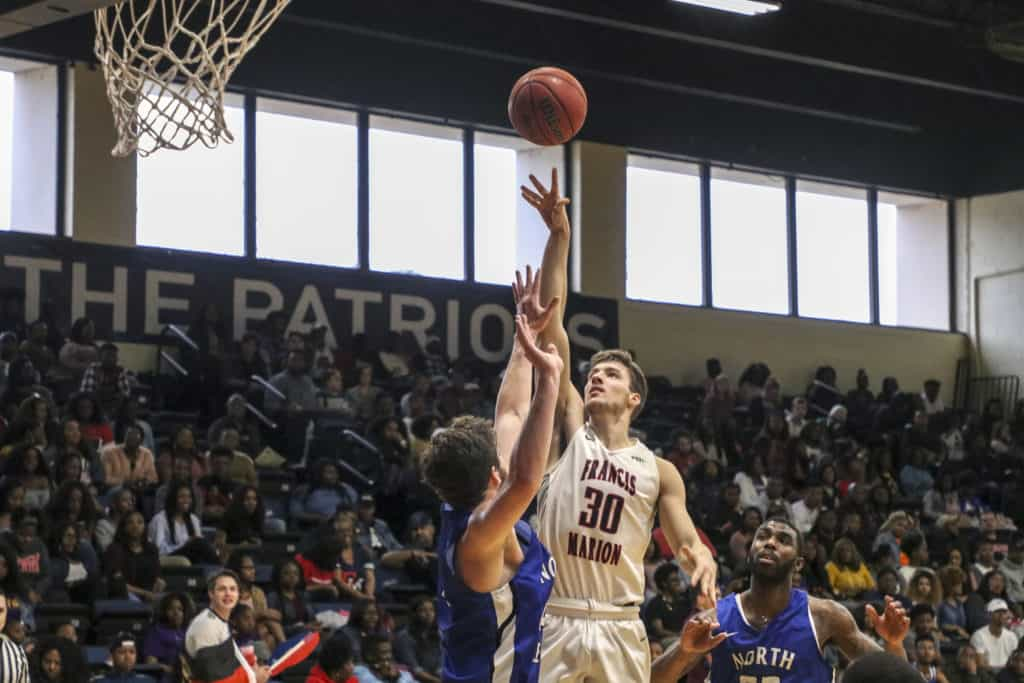 Basketball player shooting a basketball into a hoop