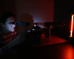 A student uses a tool to investigate a light in a dark room.