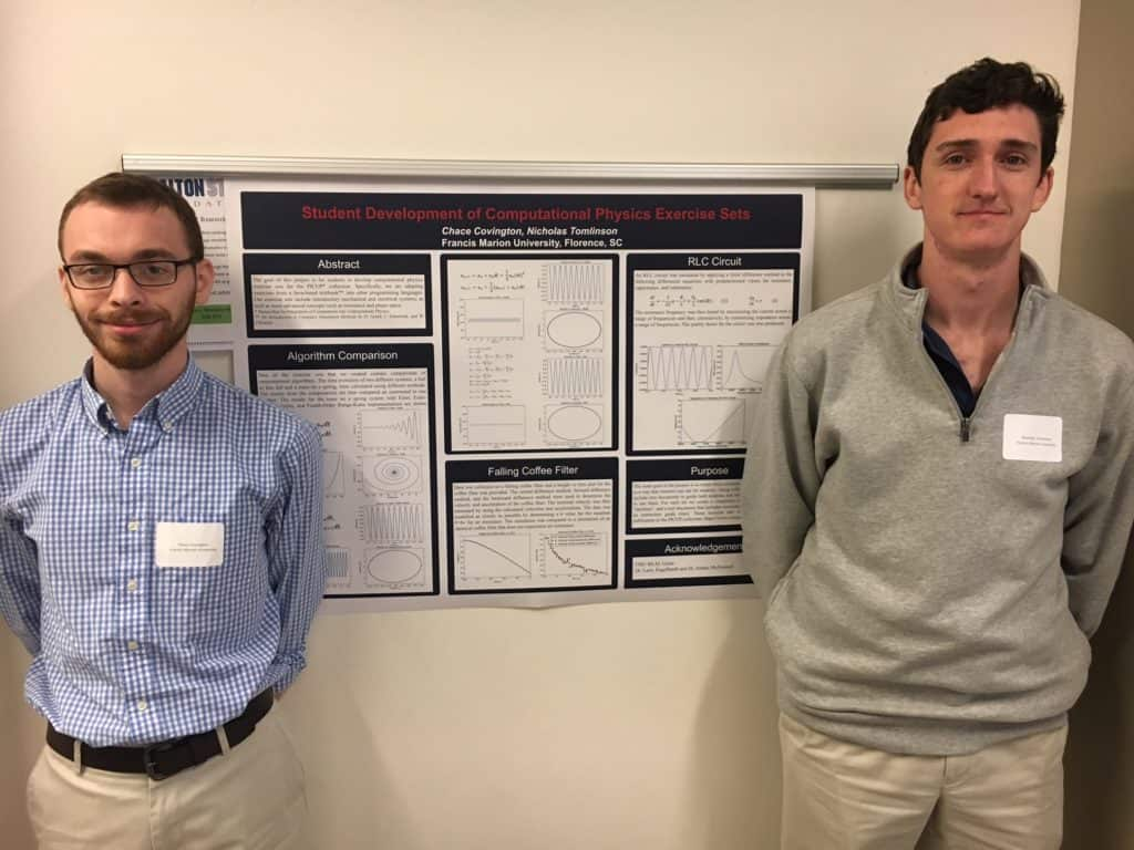 Two students standing with their research board