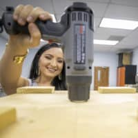 FMU 2019 graduate Taylor Watson sits in an Industrial Engineering lab with a drill.