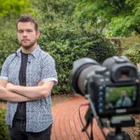 FMU graduate Garrett Fuller poses in front of a camera