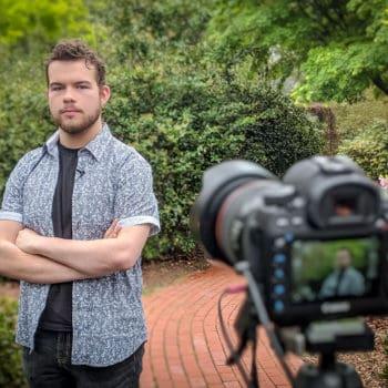 FMU graduate Garrett Fuller poses in front of a camera