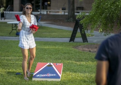 Two students play cornhole during a cookout on the UC lawn.