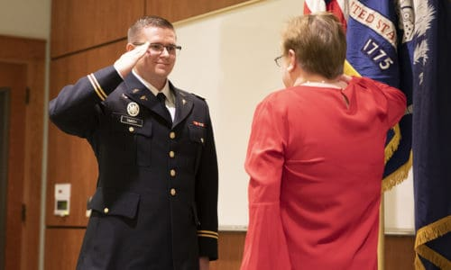 Second Lieutenant Nicholas Smith receives is first salute from his mother Retired Petty Office Kathleen Smith.