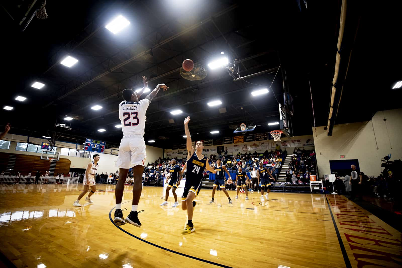 An FMU Patriot makes a shot during a basketball game.