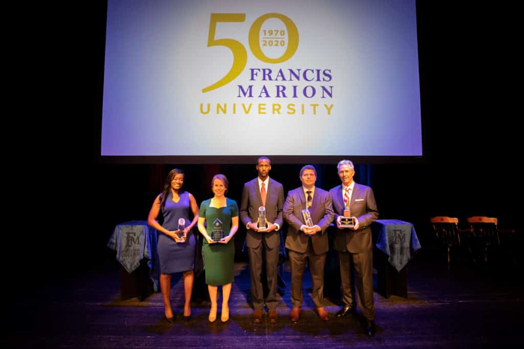 FMU's Alumni Award winners pose for a photo on the stage of the FMU PAC.