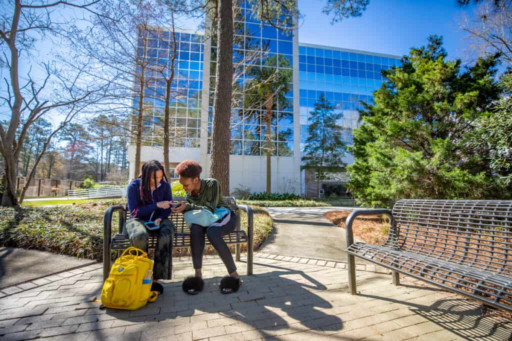 Two FMU students sit on a bench on a sunny day near the Leatherman Science Facility on FMU's campus.