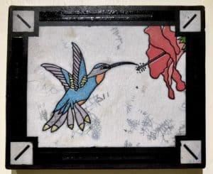 A ceramic piece depicting a feeding hummingbird.