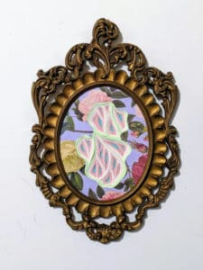 A paper piece depicting a modern design on old wallpaper within a picture frame.