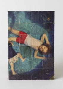 An image on wood piece depicting children resting in a pool.