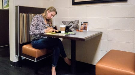 A students sits at a booth in Cauthen Cafe on FMU's main campus.